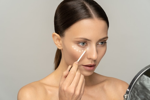 Woman with natural makeup applying concealer on flawless fresh skin, doing make up looking at mirror