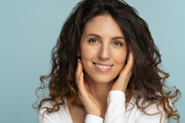 Woman with natural makeup, curly hair, touching well-groomed pure skin on face, isolated on blue background