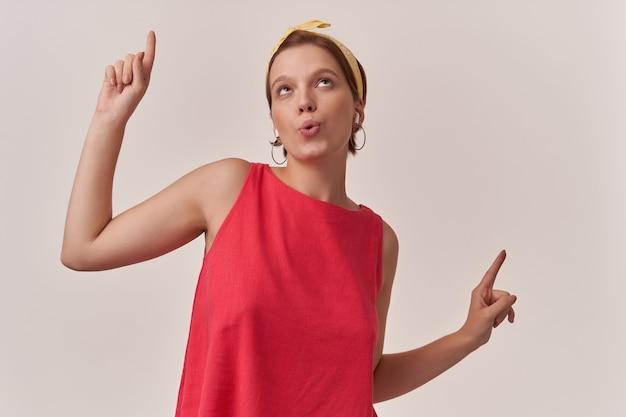 スタイリッシュな夏の流行の赤いドレスと黄色のバンダナポーズを身に着けているナチュラルメイクの女性