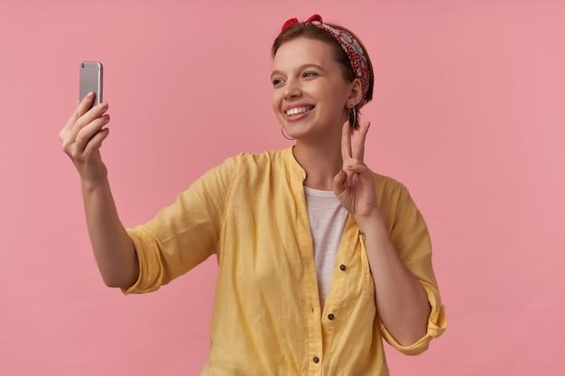 ピンクでポーズをとる流行の夏を身に着けているナチュラルメイクの女性