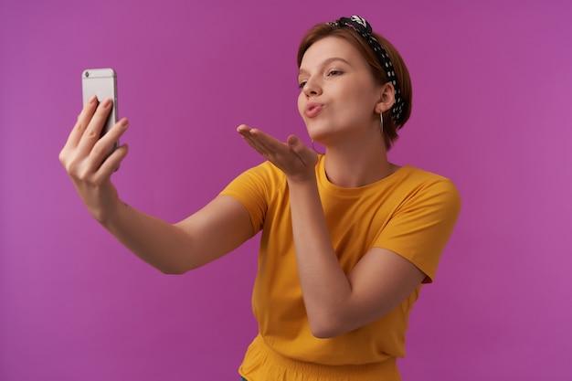 黄色いシャツと黒いバンダナの感情を身に着けているナチュラルメイクの女性が愛情をいちゃつくとエアキスを送信し、紫色でポーズをとって電話でショットを作る