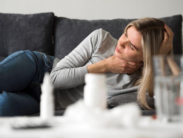 ソファに首の痛みを持つ女性