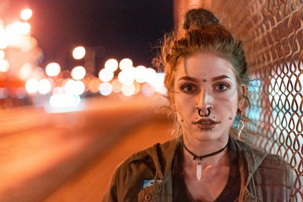 Женщина с пирсингом в носу в ночное время