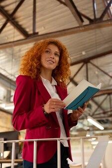 ノートを持つ女性。日を計画しながらノートを保持ピンクのジャケットを着ている実業家
