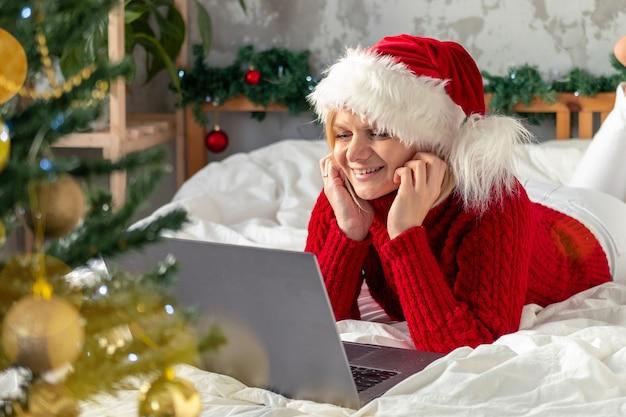 サンタの帽子で自宅にノートパソコンを持つ女性