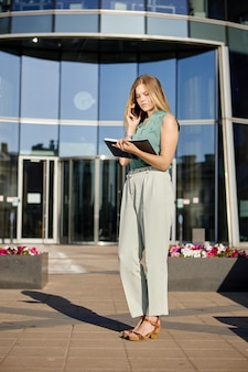 사무실 센터 근처에서 스마트폰으로 노트북 회담을 하는 여성