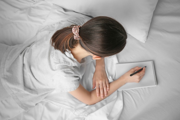Woman with notebook writing on the bed, top view