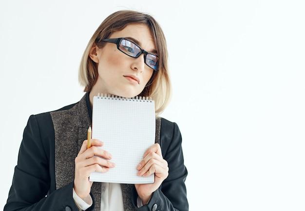 Женщина с блокнотом в руках классический костюм очки крупным планом модель