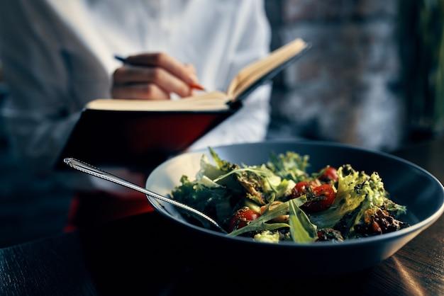 窓の近くにメモ帳とプレートトマトの新鮮な野菜のサラダを持つ女性