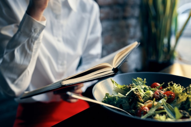 Woman with notepad near the window and salad in a plate tomatoes fresh vegetables