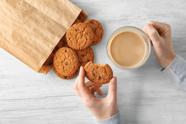 Woman with oatmeal cookies and cup of coffee at wooden table