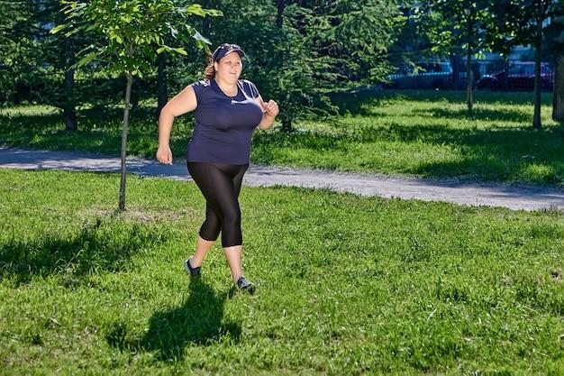 화창한 여름날 공공 공원에서 조깅하는 비만 여성