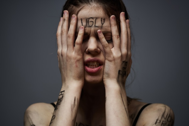 Woman with offensive inscriptions on her body touching herself with hands stress frustration