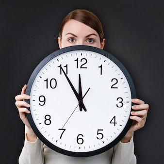 Woman with an office clock against chalkboard background
