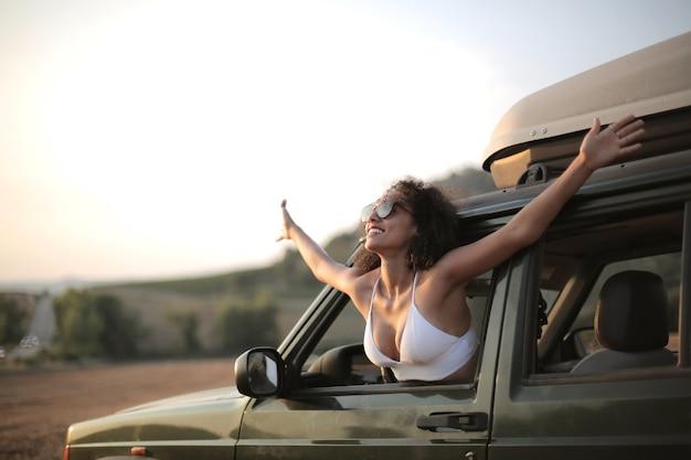 車の窓の外を見ている開いた手を持つ女性