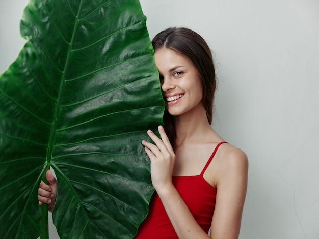 彼女の前に緑の葉を保持している水着で口を開けた女性