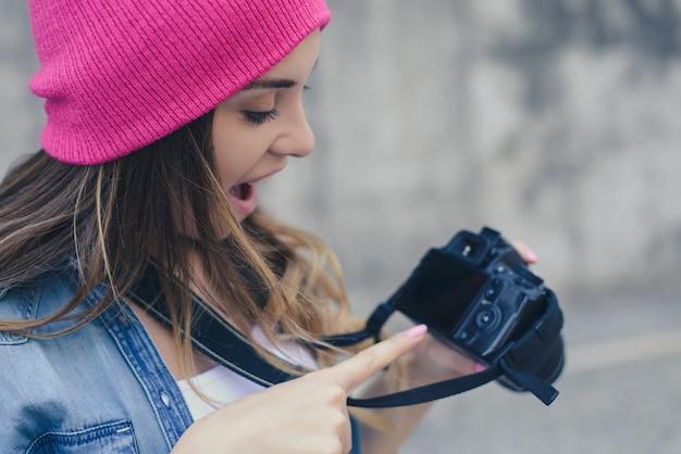灰色の背景にカメラを指しているピンクの帽子で口を開けた女性