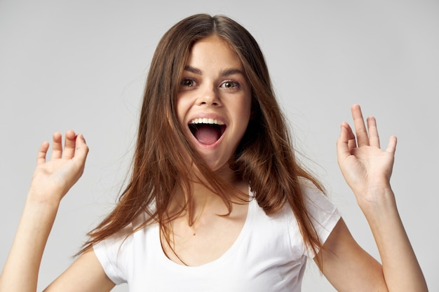 手で白いtシャツの感情ジェスチャーで口を開けて女性