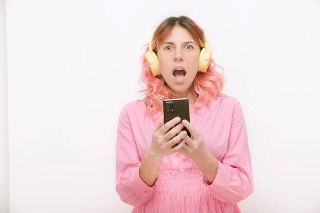 흰색 배경에 헤드폰과 휴대전화를 들고 경외심에 카메라를 바라보는 입을 벌린 여성