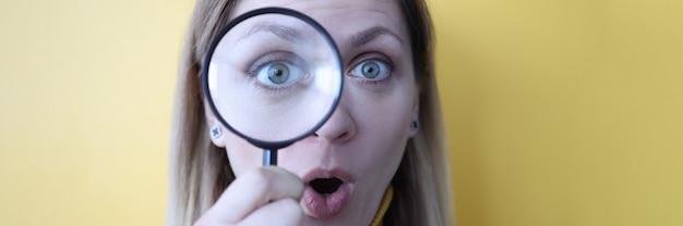 虫眼鏡を通して見ている開いた口を持つ女性