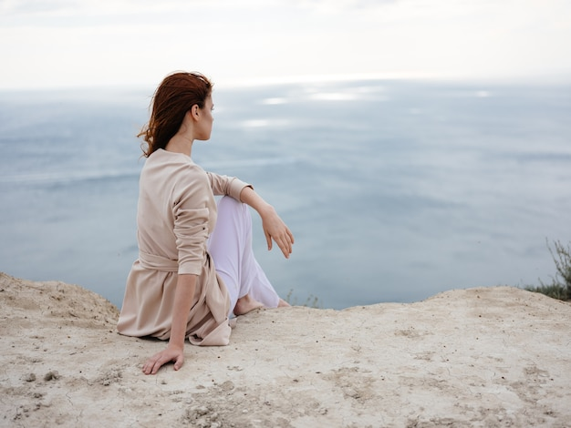 A woman with outerwear sits on a stone hill and the ocean in the background. high quality photo