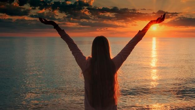 海のクレーンショットで夕日の美しさを楽しんでいる腕を伸ばした女性