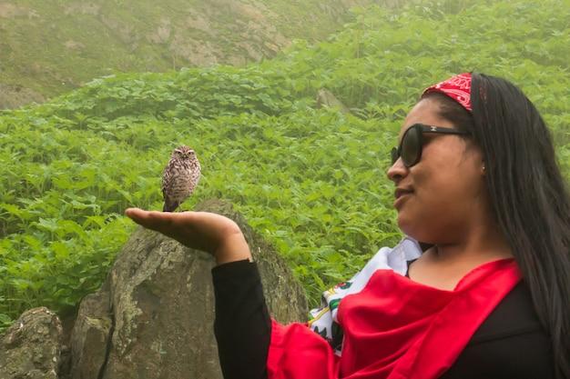 Женщина с протянутой рукой делает вид, что держит сову посреди пейзажа
