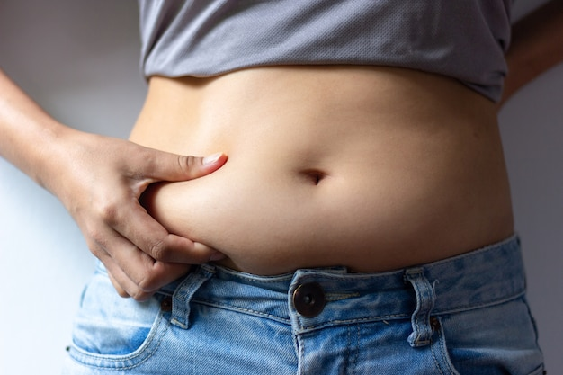 Woman with overweight abdomen. hand holding excessive fat belly