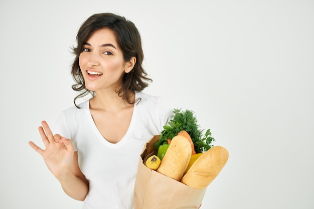 Woman with a package of groceries vegetables healthy eating positive hand gesture
