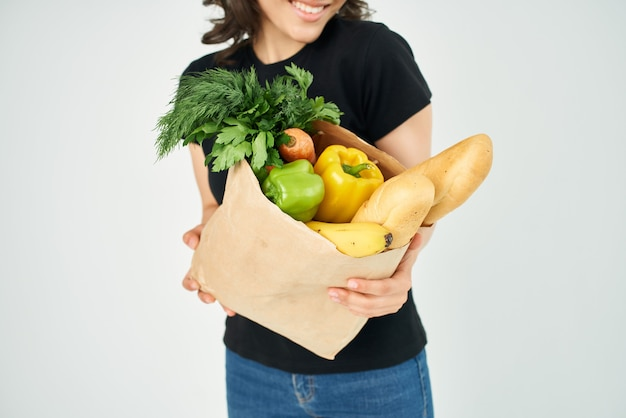 Woman with a package of products in the hands of vegetables with healthy food closeup
