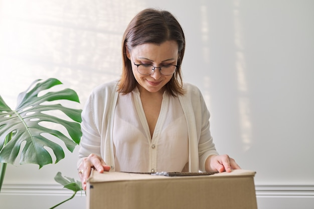 Woman with packaged package, cardboard box. service for international postal delivery, auto delivery of goods