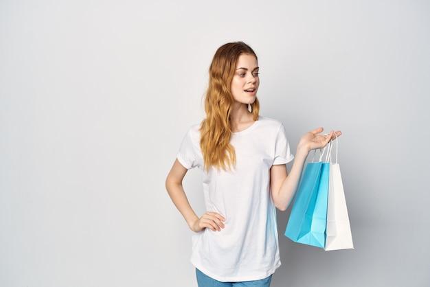 Женщина с пакетами в руках покупки развлечений весело светлый фон