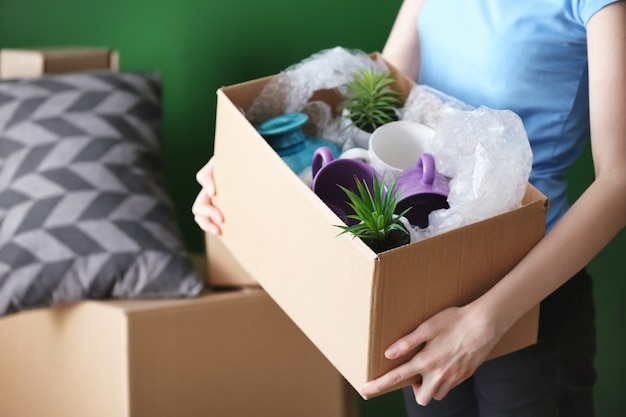 屋内にパックされたカートンボックスを持つ女性。引っ越しの家のコンセプト