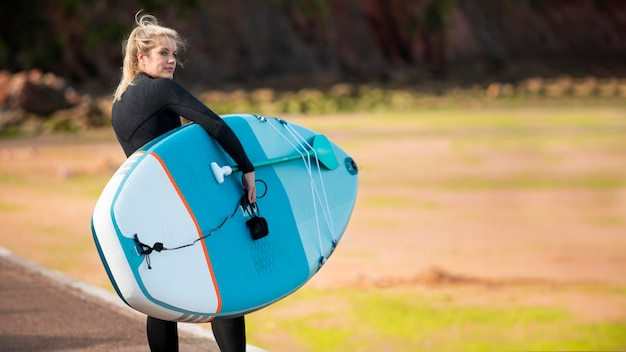 海辺でパドルボードを持つ女性