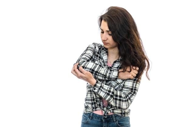 白い背景で隔離の肘の痛みを持つ女性