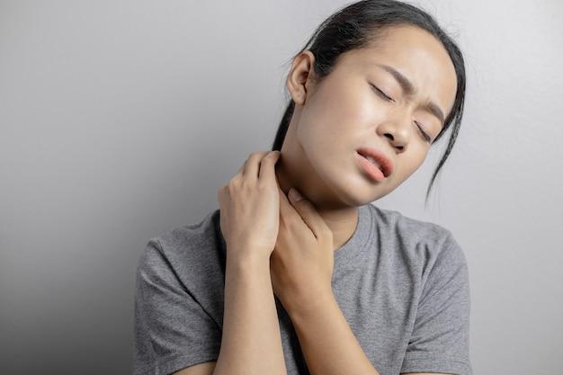 목에 통증이 있는 여자. 목의 통증으로 고통받는 개념 여자.