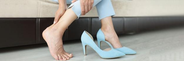 Женщина с болезненными ощущениями в ногах сидит на диване без обуви
