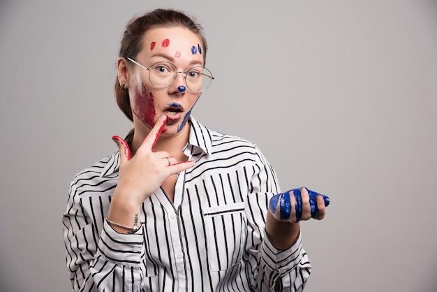 Donna con vernici sul viso e occhiali su sfondo grigio