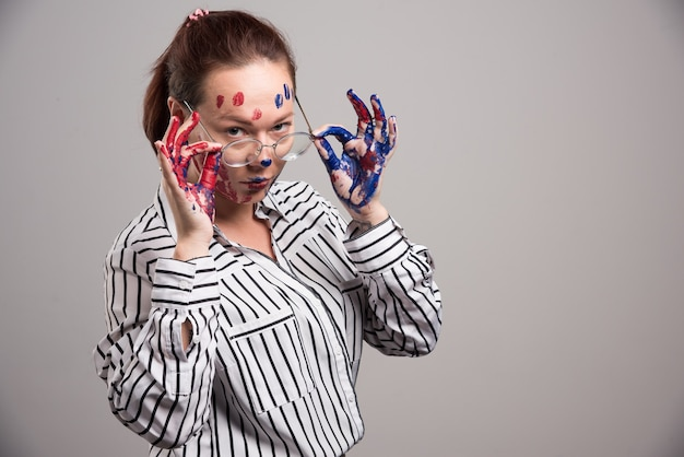 Woman with paints on her face puts on glasses on gray background
