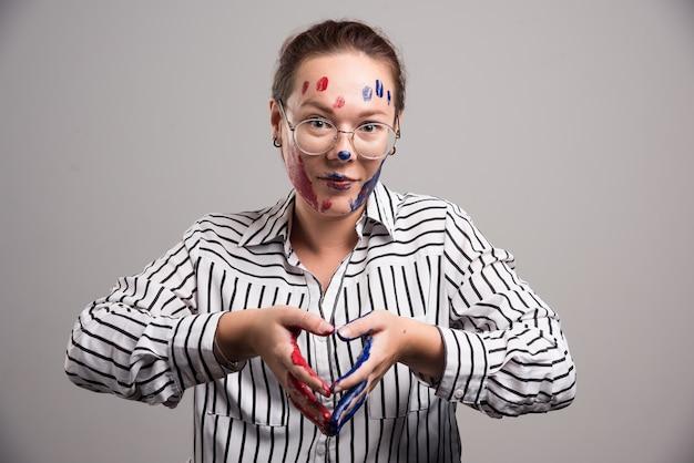 Женщина с красками на лице и очках на сером фоне