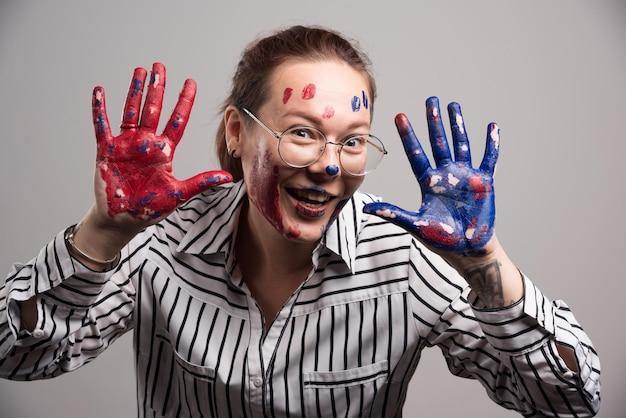顔に絵の具を塗り、灰色の眼鏡をかけた女性