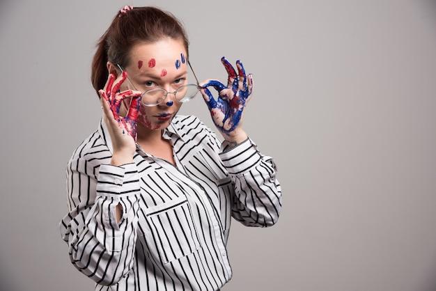 Женщина с красками на лице надевает очки на сером фоне