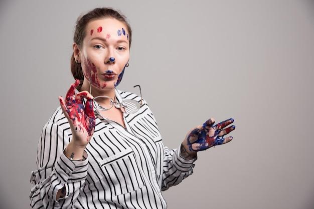 Женщина с красками на лице надевает очки на серый