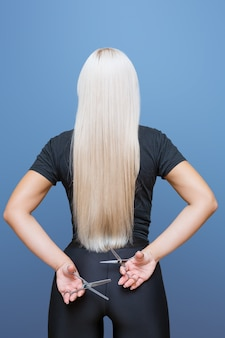 Woman with  pair of scissors stands back and cuts her long blond hair. the concept of a professional hairdresser and hair care