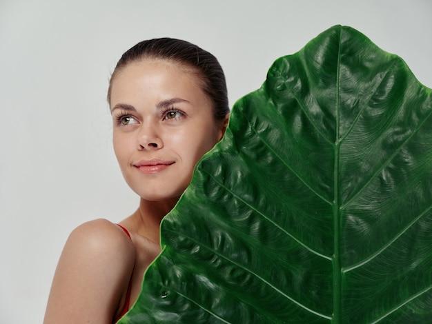ヤシの葉の裸の肩の側面図孤立した背景を持つ女性。高品質の写真