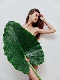 야자수 잎을 가진 여자가 벗은 몸을 매력적인 모습으로 덮습니다.