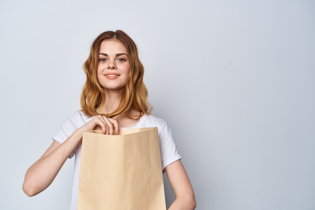 Woman with paper bag in her hands shopping fun light background