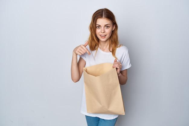 彼女の手で紙袋をショッピング楽しい明るい背景を持つ女性