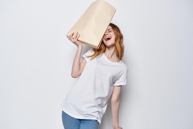그녀의 손에 종이 가방을 들고 재미있는 밝은 배경 쇼핑을 하는 여자