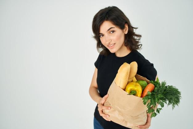 야채 건강 식품을 배달하는 손에 식료품의 종이 봉지를 가진 여자